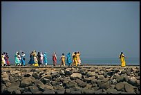 Women walking on  jetty in the distance, Elephanta Island. Mumbai, Maharashtra, India