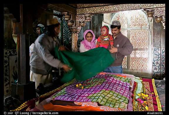 Family making offering inside Shaikh Salim Chishti mausoleum. Fatehpur Sikri, Uttar Pradesh, India (color)