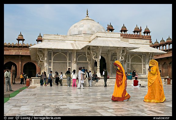 Two women walking outside the white marble  Shaikh Salim Chishti tomb. Fatehpur Sikri, Uttar Pradesh, India (color)