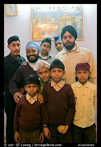 Sikh men and boys in front of picture of the Golden Temple. Bharatpur, Rajasthan, India (color)
