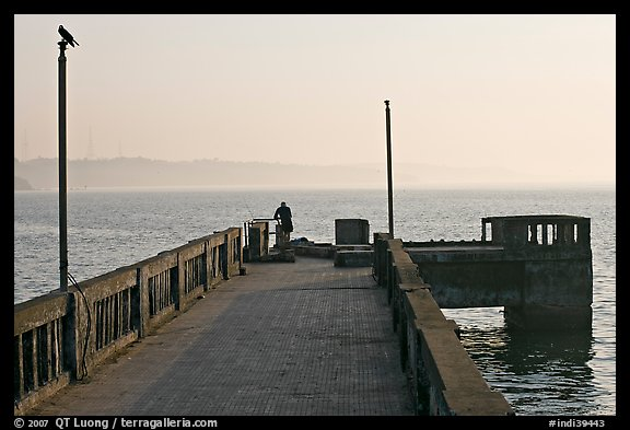 Pier with man fishing, early morning, Dona Paula. Goa, India (color)