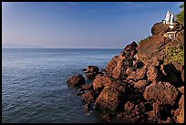 Boulders and christian statues at the edge of ocean, Dona Paula. Goa, India (color)