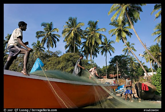 Men mending fishing net with palm trees in background. Goa, India (color)