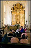 Indian women sitting in front of the altar, Basilica of Bom Jesus, Old Goa. Goa, India (color)