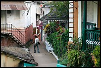Man in alley with gardens, Panjim. Goa, India