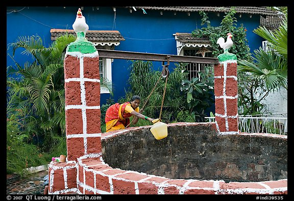 Woman retrieving water from well with blue house behind, Panjim. Goa, India (color)