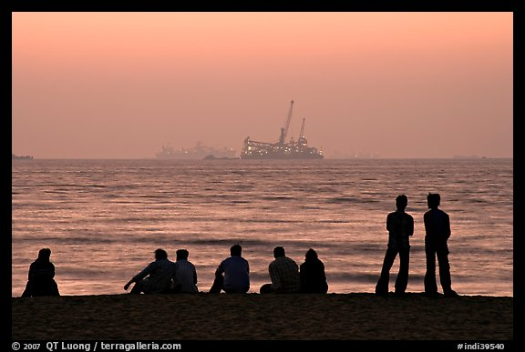People and  off-shore platforms, Miramar Beach, sunset. Goa, India (color)
