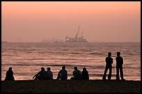 People and  off-shore platforms, Miramar Beach, sunset. Goa, India
