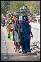 Women walking in line carrying baskets on heads. Khajuraho, Madhya Pradesh, India (color)