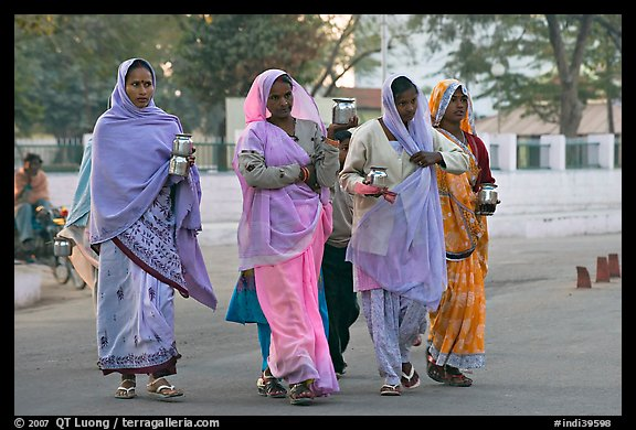 Hindu women walking in street with pots. Khajuraho, Madhya Pradesh, India (color)