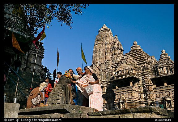 Worshippers making offering at Matangesvara temple with  Lakshmana behind. Khajuraho, Madhya Pradesh, India (color)