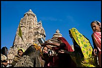 Hindu women making offerings to image with Lakshmana temple behind. Khajuraho, Madhya Pradesh, India (color)