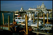 Water taxi driver cleaning out his boat in the morning, Santa Maria della Salute in the background. Venice, Veneto, Italy ( color)