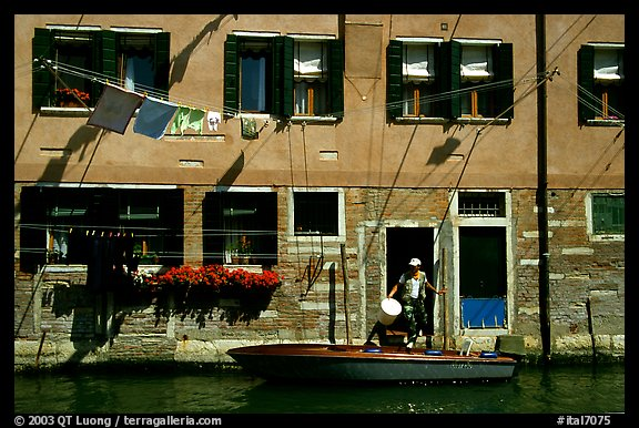 Resident stepping from his boat to his house,  Castello. Venice, Veneto, Italy (color)