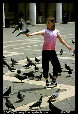 Girl playing with the pigeons, Piazzetta San Marco (Square Saint Mark), mid-day. Venice, Veneto, Italy (color)