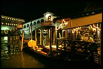 Gondolier and gondola, Rialto Bridge at night. Venice, Veneto, Italy