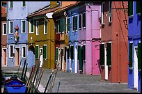 Sidewalk and row of brightly painted houses, Burano. Venice, Veneto, Italy