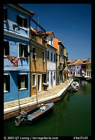 Canal surrounded by houses painted  a multitude of bright colors, Burano. Venice, Veneto, Italy (color)