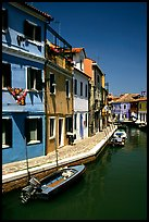 Canal surrounded by houses painted  a multitude of bright colors, Burano. Venice, Veneto, Italy ( color)