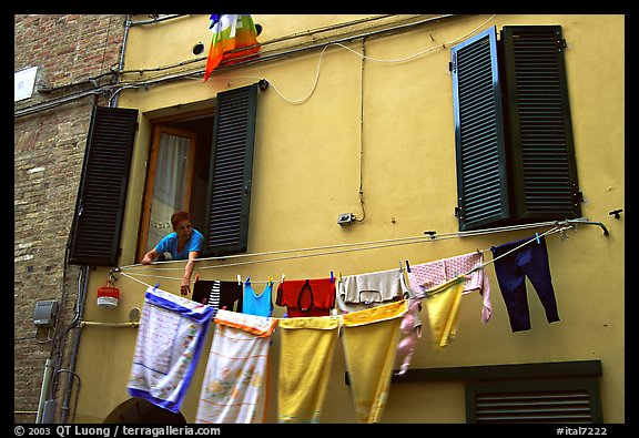 Woman hanging laundry. Siena, Tuscany, Italy (color)