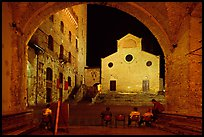 Duomo framed by an arch at night. San Gimignano, Tuscany, Italy