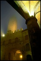 Medieval towers above Piazza del Duomo, foggy night. San Gimignano, Tuscany, Italy