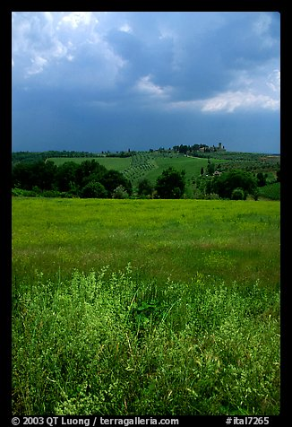 Field and distant village under storm skies. Tuscany, Italy (color)