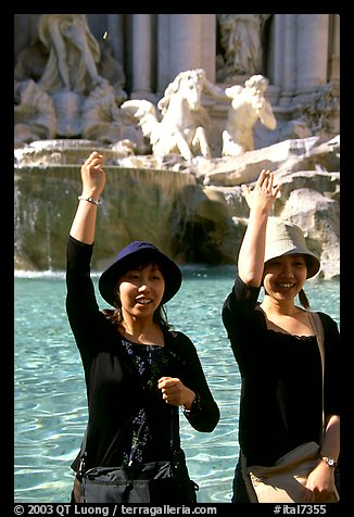 Asian tourists toss a coin over their shoulder into the Trevi Fountain. Rome, Lazio, Italy (color)