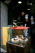 Chef at restaurant doorway with appetizers shown in glass case. Naples, Campania, Italy