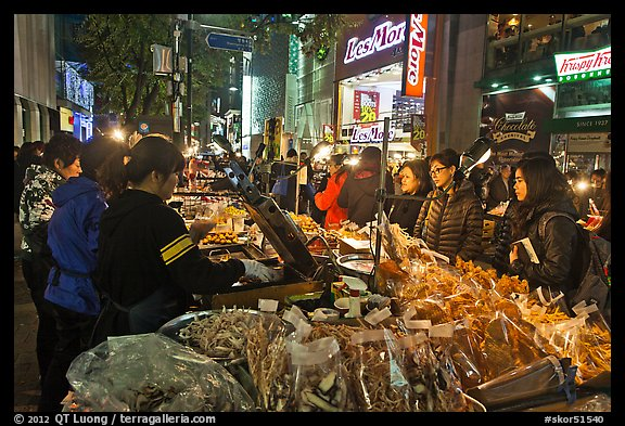 Unusual street foods on busy shopping street. Seoul, South Korea (color)