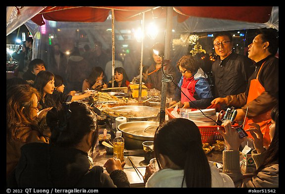 People eating noodles in a tent at night. Seoul, South Korea (color)