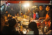 People eating noodles in a tent at night. Seoul, South Korea ( color)