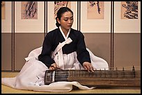 Woman playing traditional instrument. South Korea ( color)