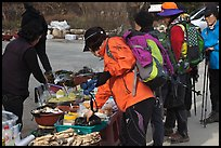 Hikers check out stand selling natural products. South Korea (color)