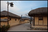 Alley bordered by straw roofed houses. Hahoe Folk Village, South Korea (color)