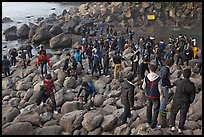 Crowd on rocky beach, Seogwipo. Jeju Island, South Korea (color)