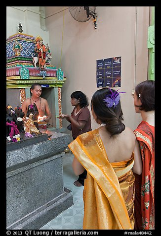 Holy man distributes fire to women, Sri Mariamman Temple. George Town, Penang, Malaysia (color)
