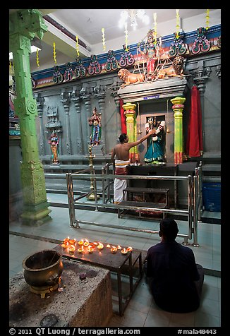 Holy man tends to altar, Hindu temple. George Town, Penang, Malaysia