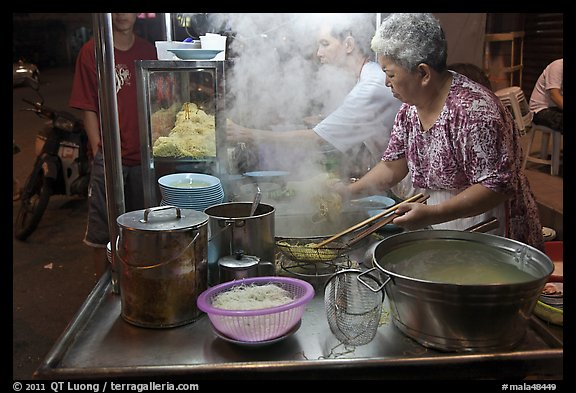 Noddles prepared on foodstall by night. George Town, Penang, Malaysia (color)