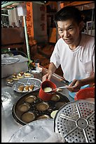Man preparing mini-pancakes. George Town, Penang, Malaysia ( color)