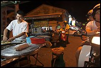 Man preparing food as people wait on motorbike. George Town, Penang, Malaysia ( color)