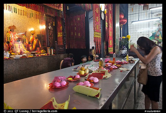 Woman Worshiping inside Chinese temple. George Town, Penang, Malaysia (color)
