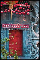 Red paper lanters, door, and stone carved wall, Hainan Temple. George Town, Penang, Malaysia (color)