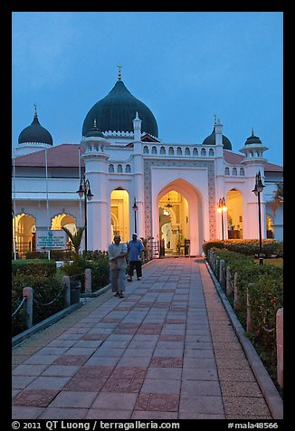 Men walking out of Masjid Kapitan Keling at dawn. George Town, Penang, Malaysia (color)