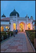 Men walking out of Masjid Kapitan Keling at dawn. George Town, Penang, Malaysia
