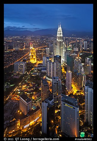Skyscrappers dominated by Petronas Towers at night. Kuala Lumpur, Malaysia (color)