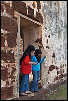 Malay girls exit on St Paul church doorway. Malacca City, Malaysia