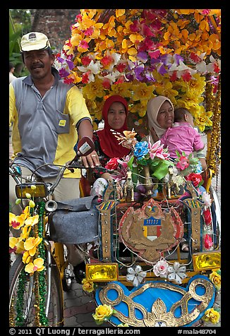 Decorated trishaw driver and passengers. Malacca City, Malaysia (color)