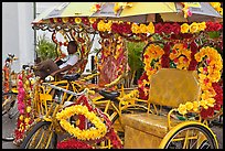Trishaws decorated with plastic flowers. Malacca City, Malaysia ( color)