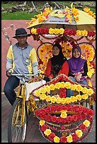 Rider and two women passengers, bicycle rickshaw. Malacca City, Malaysia